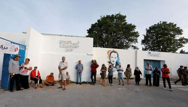 People wait to cast their vote outside a polling station during presidential election in Tunis, Tuni
