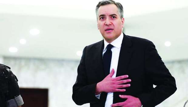 Adib gestures after saying that he is stepping down at the presidential palace in Baabda