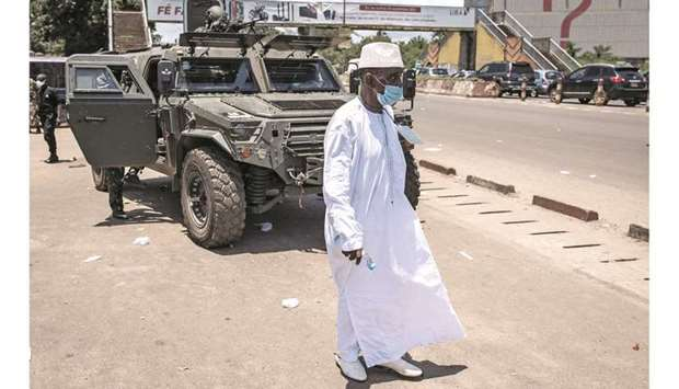 A man walks in front of an armoured military vehicle after the first session of talks between Colone
