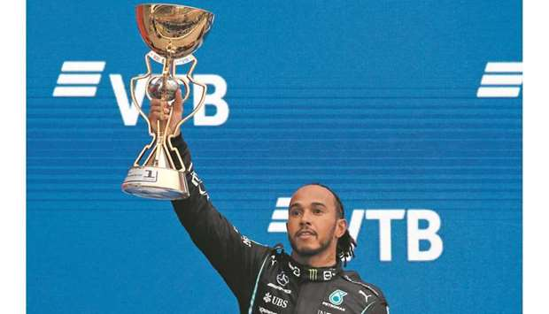 Mercedes' Lewis Hamilton celebrates with the trophy after winning the Russian Grand Prix in Sochi ye