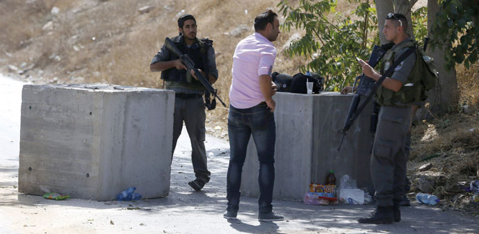 Israeli border guards check the documents of a Palestinian at a roadblock set up on a road close to