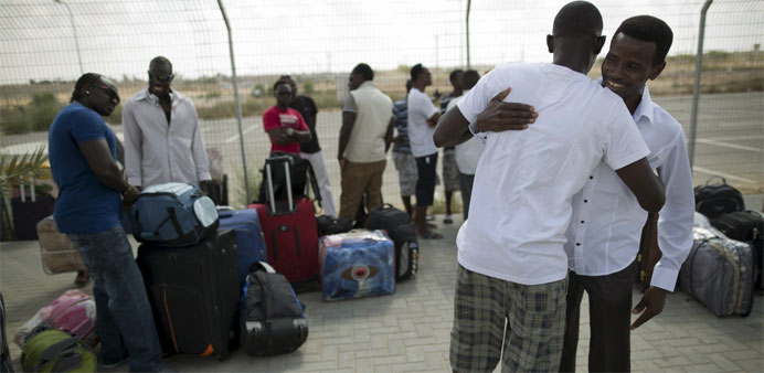 African migrants embrace after being released from Holot detention centre in Israel's southern Negev