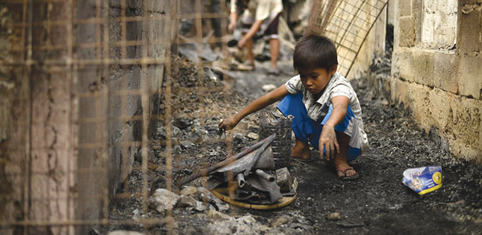 A child searches for recyclable materials after the fire.
