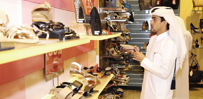 An MEC official inspects the prices of shoes.
