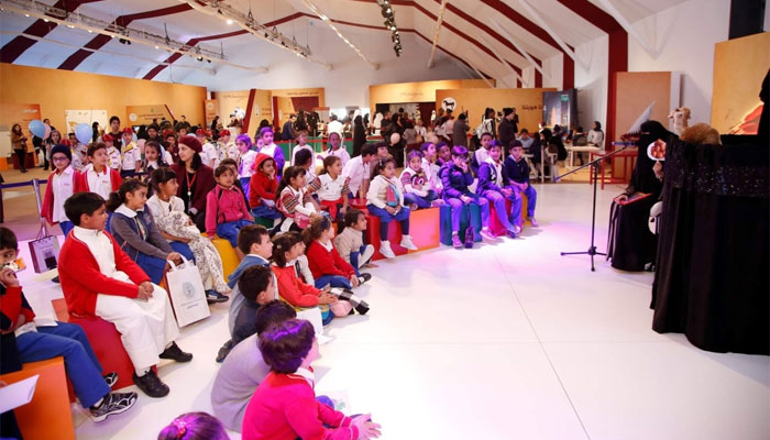 Children watching a puppet show in the QF tent at Darb Al Saai.