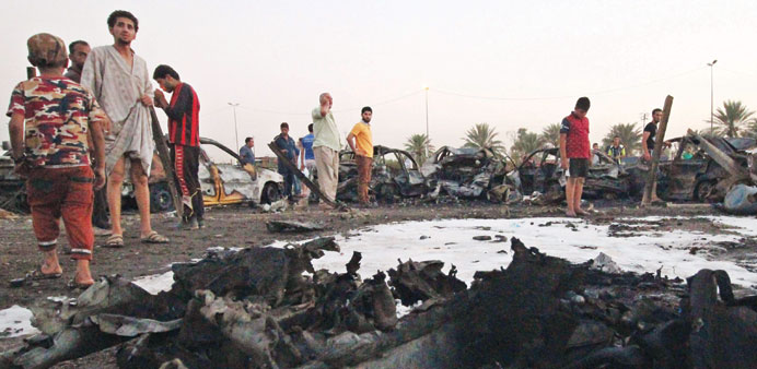 People look at the damage following a car bombing at a vehicle market in Baghdad's Shia district of