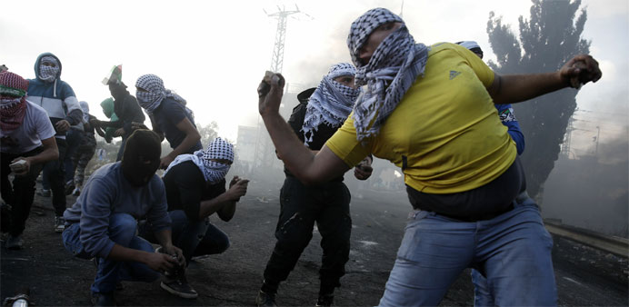 Palestinian protesters throw stones during clashes with Israeli security forces
