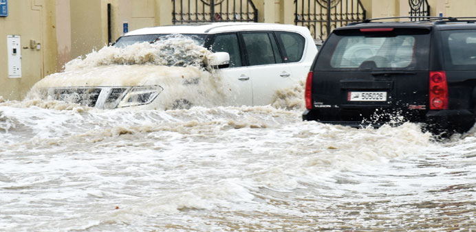 Vehicles wading through a heavily flooded street in Doha. PICTURE: Noushad Thekkayil