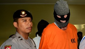 David Fox is escorted by police after a press conference at a police station in Denpasar