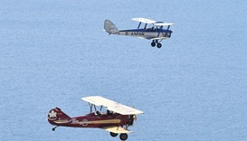 A Tiger Moth (top) and a Travel Air 4000 biplane fly during a photocall for the launch of the Vintag