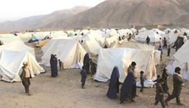 Afghans displaced by ongoing fighting against Taliban militants walk inside a makeshift camp in Takh
