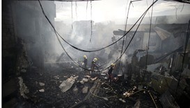 Firemen extinguish the fire at a fireworks shop in Bocaue, Bulacan, north of Manila