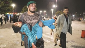 An Afghan man carrying a wounded girl after an attack by gunmen at the Karte Sakhi shrine in Kabul.