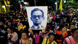 Well-wishers hold a picture of Thailand's King Bhumibol Adulyadej