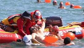 The swimmer, who later died in hospital, is pulled onto a boat during the annual harbour race
