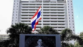 The Thai national flag flies at half mast in the backdrop of a portrait of late King Bhumibol