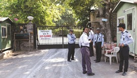 Private security guards stand near a banner placed at the main gate of the Delhi zoo which has tempo