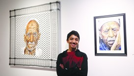 Mohamed Qraiqea, with two of his paintings