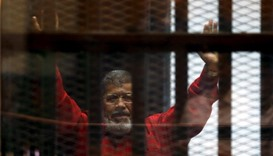 Egypt's deposed president Mohamed Mursi greets his lawyers and people from behind bars