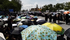 Thousands of mourners clad in black shelter under umbrellas in front of the Grand Palace