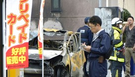Policemen and firefighters investigate a parking lot after an explosion in Utsunomiya, Japan