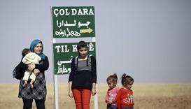A Kurdish woman stands with heir children at the entrance of the village of Joldara