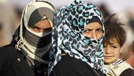Iraqi refugee women who fled Mosul wait to enter Syria in Rajam al-Saliba