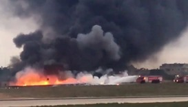 fire trucks aiming their hoses at the burning wreckage of a small plane which crashed Valletta