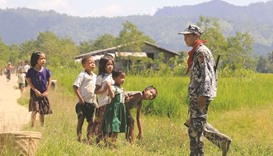 A recent photo shows Myo ethnic children look at a Myanmar border police in LaungDon, located in Rak