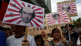 Pro-China protesters carry printouts depicting legislator-elects Baggio Leung (L, R) and Yau Wai-chi