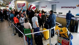People line up in front of a counter of Lufthansa's budget airlines Eurowings and Germanwings during