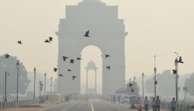 Pedestrians walk near the India Gate monument amid heavy smog in New Delhi