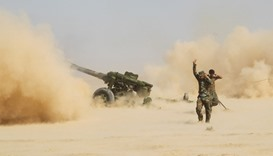 PMF personnel fire artillery during clashes with Islamic State militants south of Mosul