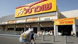 A man pushes a shopping cart outside Shufersal, Israel's largest supermarket chain, in West Bank