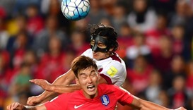 South Korea's Jang Hyun-Soo (front) fights for the ball with Qatar's Sebastian Soria (back)