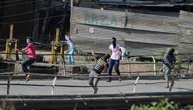 Kashmiri protestors throw stones towards police in clashes during a protest against the death of civ
