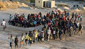 Migrants wait to receive food at a detention center in the coastal city of Sabratha, Libya