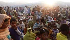 The sun rises as thousands of Rohingya refugees who fled from Myanmar a day before wait by the road