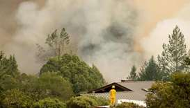 A firefighter watches smoke billow as flames approach a residential area in Sonoma in California