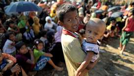 Rohingya refugees wait for humanitarian aid to be distributed at the Balukhali refugee camp in Cox's