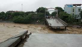 Residents standing at an end of a destroyed bridge in the northern province of Yen Bai