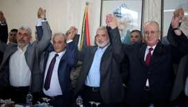 Palestinian Prime Minister Rami Hamdallah and Hamas Chief Ismail Haniyeh hold hands