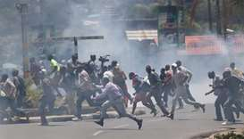 Supporters of Kenyan opposition National Super Alliance coalition run as riot policemen fire tear ga
