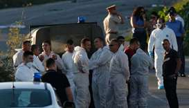 Police and forensics experts stand behind a road block after a powerful bomb blew up a car killing i