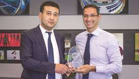 Director General of Aspire Academy Ivan Bravo (right) presents a shield to Umid Ahmadjonov, the Pres