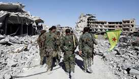 Fighters of Syrian Democratic Forces walk past the ruins of destroyed buildings near the National Ho
