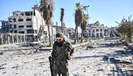 A member of the Syrian Democratic Forces (SDF) walks through a heavily damaged a street leading to a