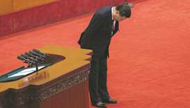 China's President Xi Jinping bows to delegates after delivering a speech at the opening session of t