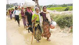 Rohingya refugees, who crossed the border from Myanmar two days earlier, walk after they received pe