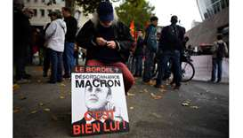A man sits by a placard prior to a demonstration called by the CGT workers' union against the French